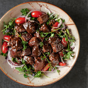 Vietnamese shaking beef in a bowl from above.