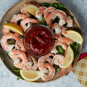 Shrimp cocktail and cocktail sauce garnished with lemons from above.