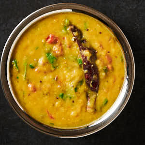 tarka dal in a metal bowl from above.