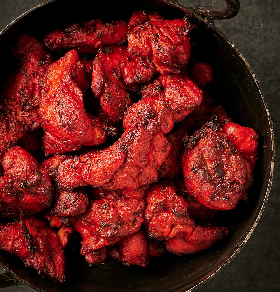 Grilled chicken tikka in a kadai from above.