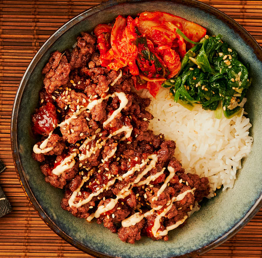 korean beef bowl with banchan and creamy Gochujang drizzle from above.