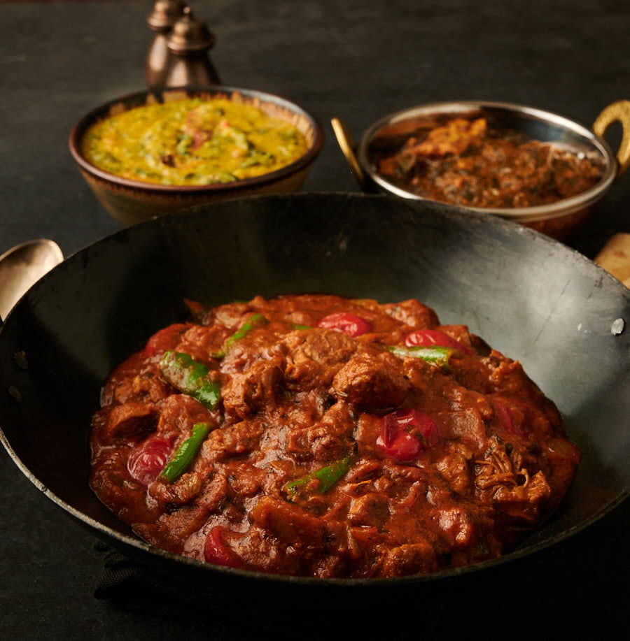 lamb bhuna in a kadai with tarka dal and chicken curry table scene from the front.