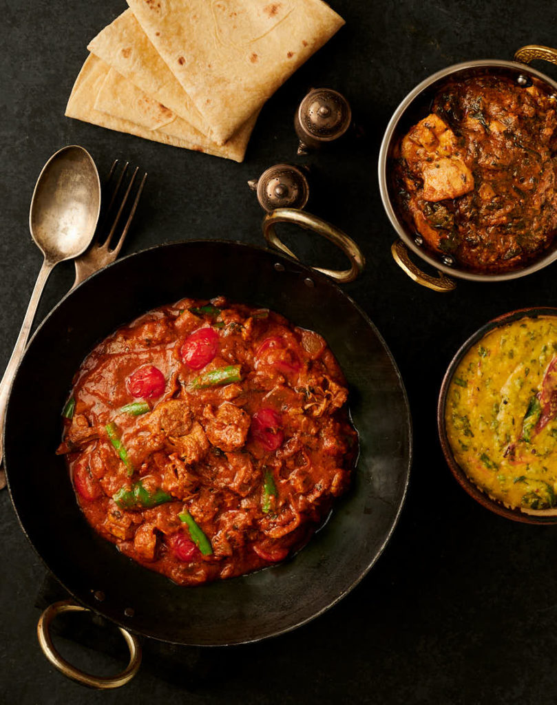 lamb bhuna, chicken curry, tarka dal and chapati table scene