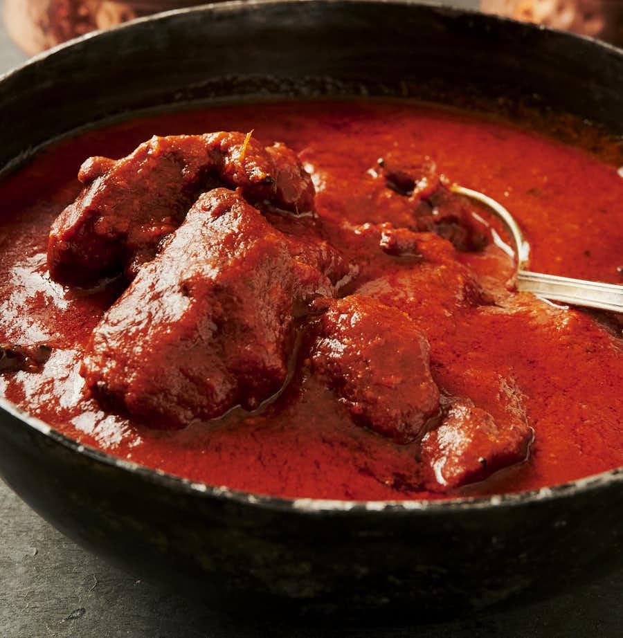 Spoon in a kadai full of chicken tikka masala