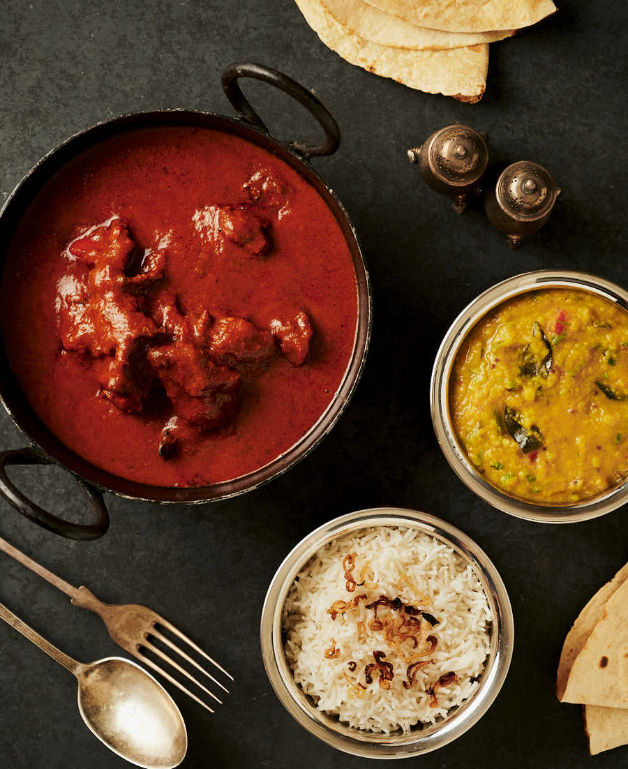 Table scene with chicken tikka masala, dal and rice.