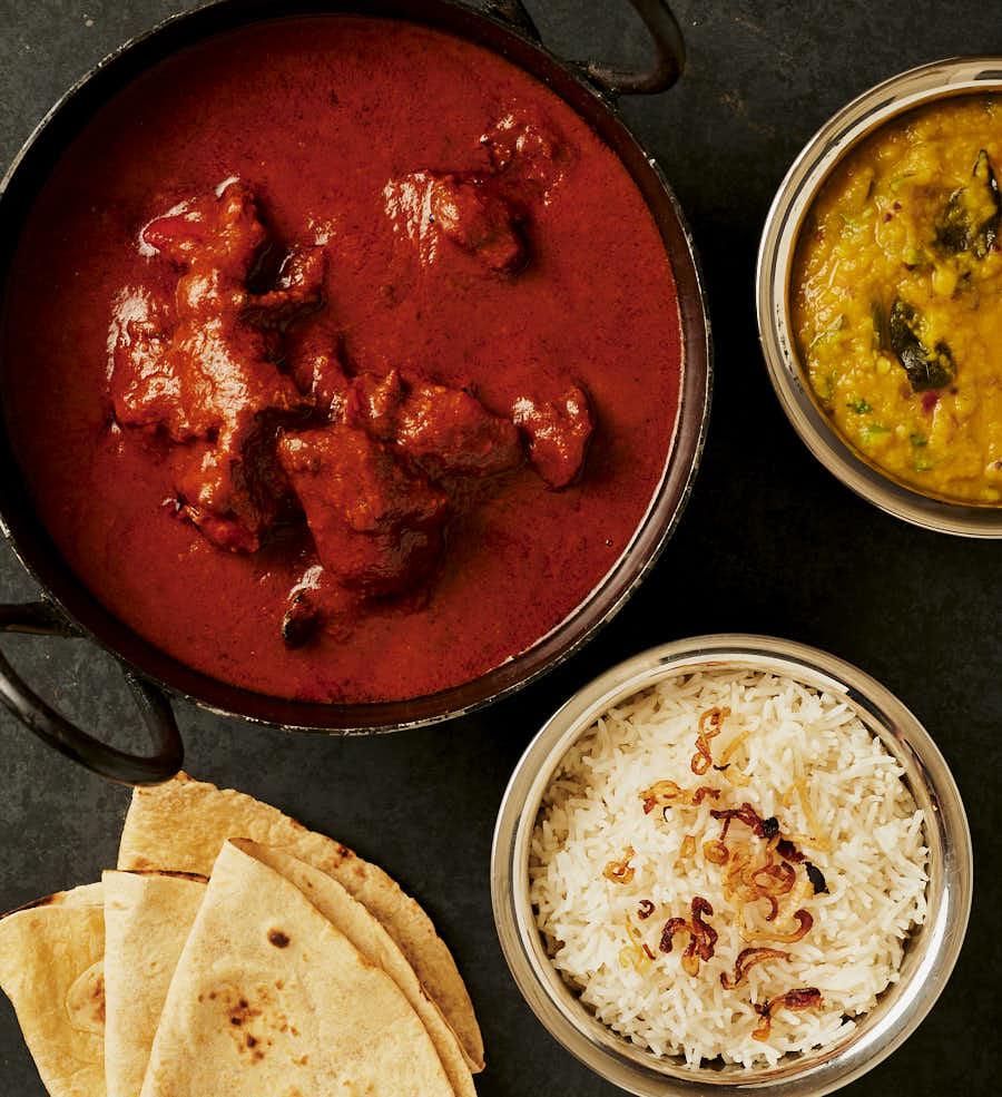Table scene - chicken tikka masala, dal, rice and chapatis.