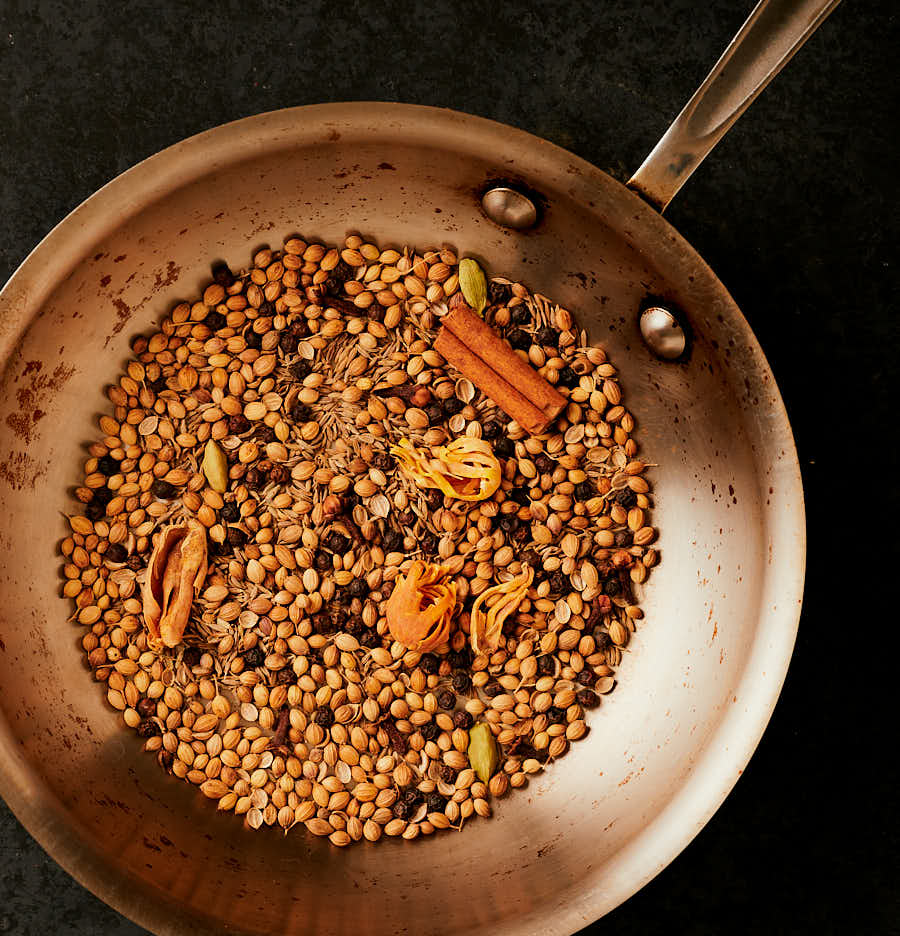 Whole spices toasting in a pan