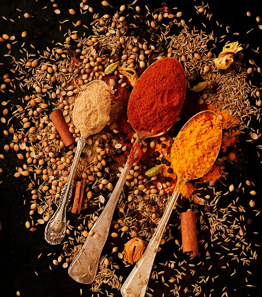 Spoons full of ground spices and scattered whole spices.