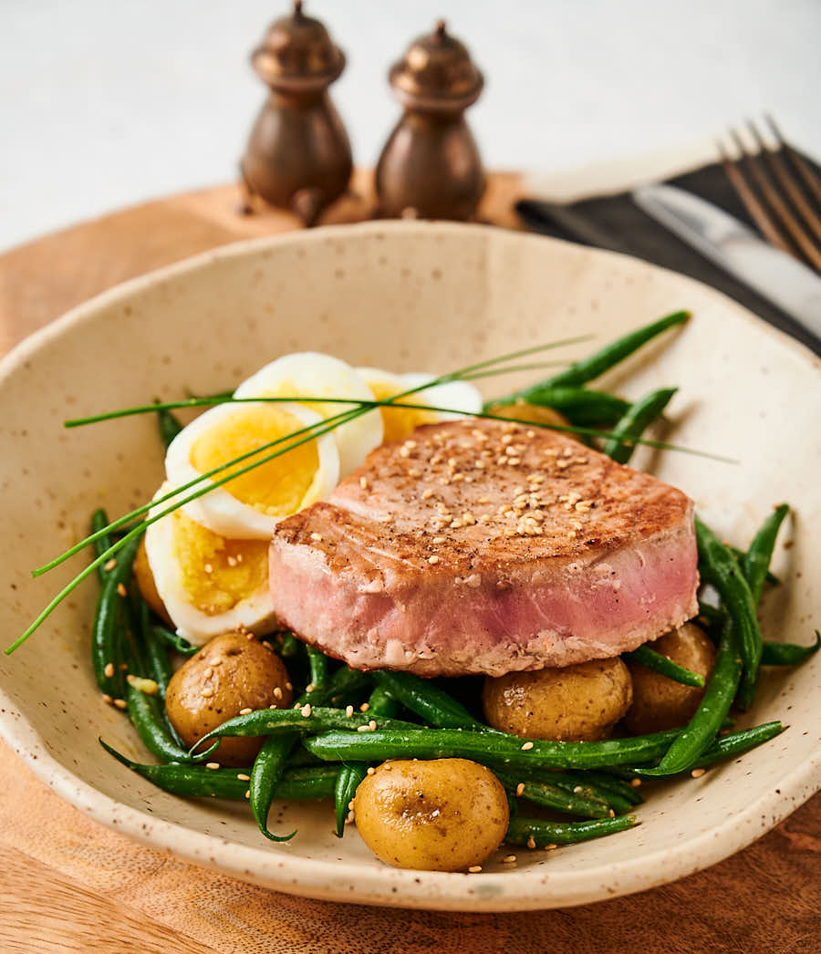 Bowl with Japanese seared tuna with beans, whole baby potatoes and sliced egg.