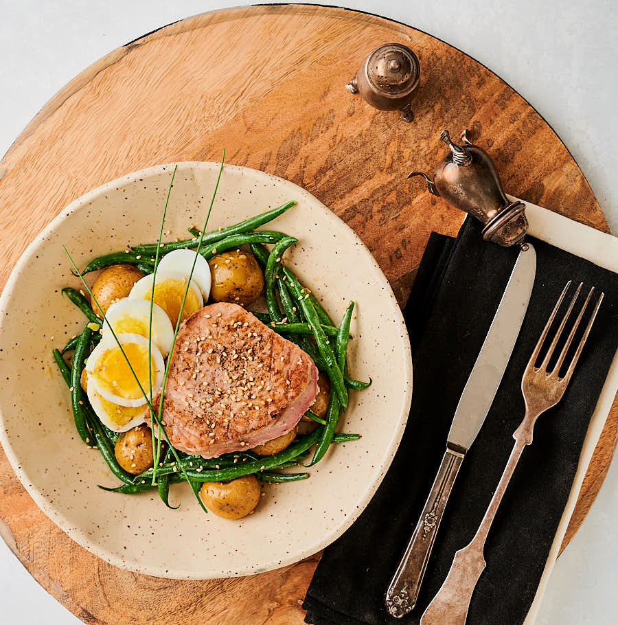 Japanese seared tuna on a bed of potatoes, green beans and sliced egg table scene.