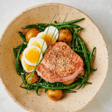 Bowl with seared Japanese tuna on a bed of green beans, potatoes and sliced egg