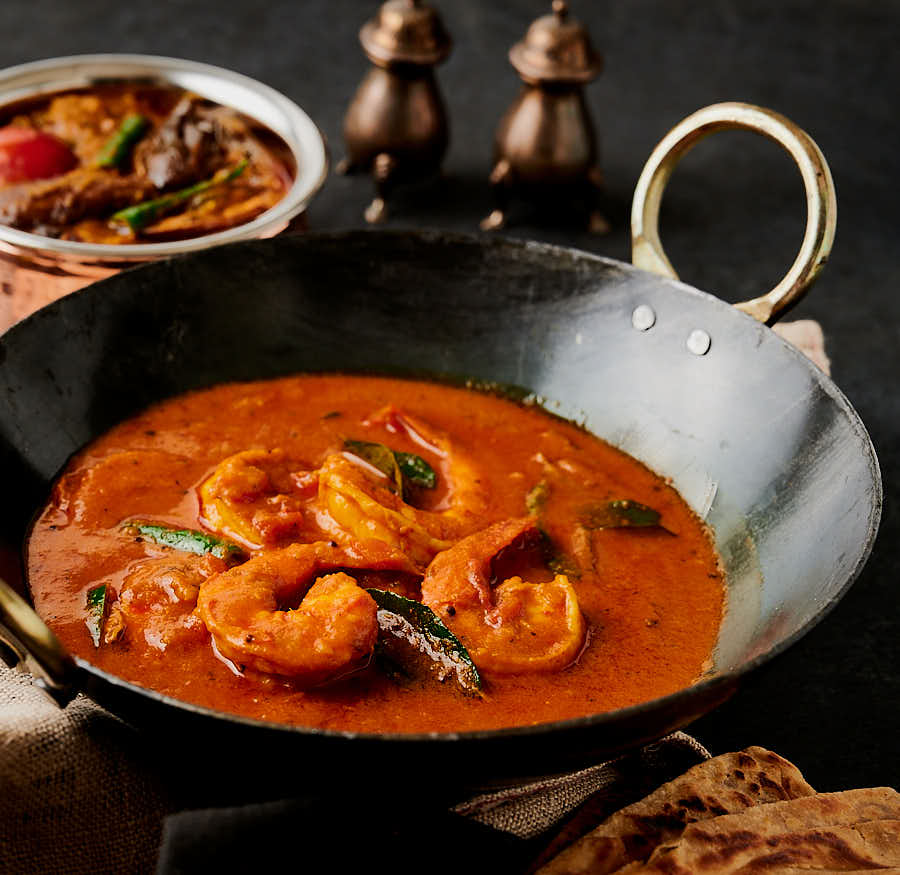 South Indian prawn curry table scene with eggplant curry.
