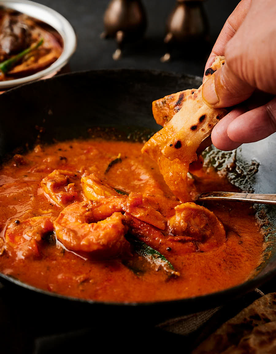 Dipping a piece of naan into prawn curry from the front.
