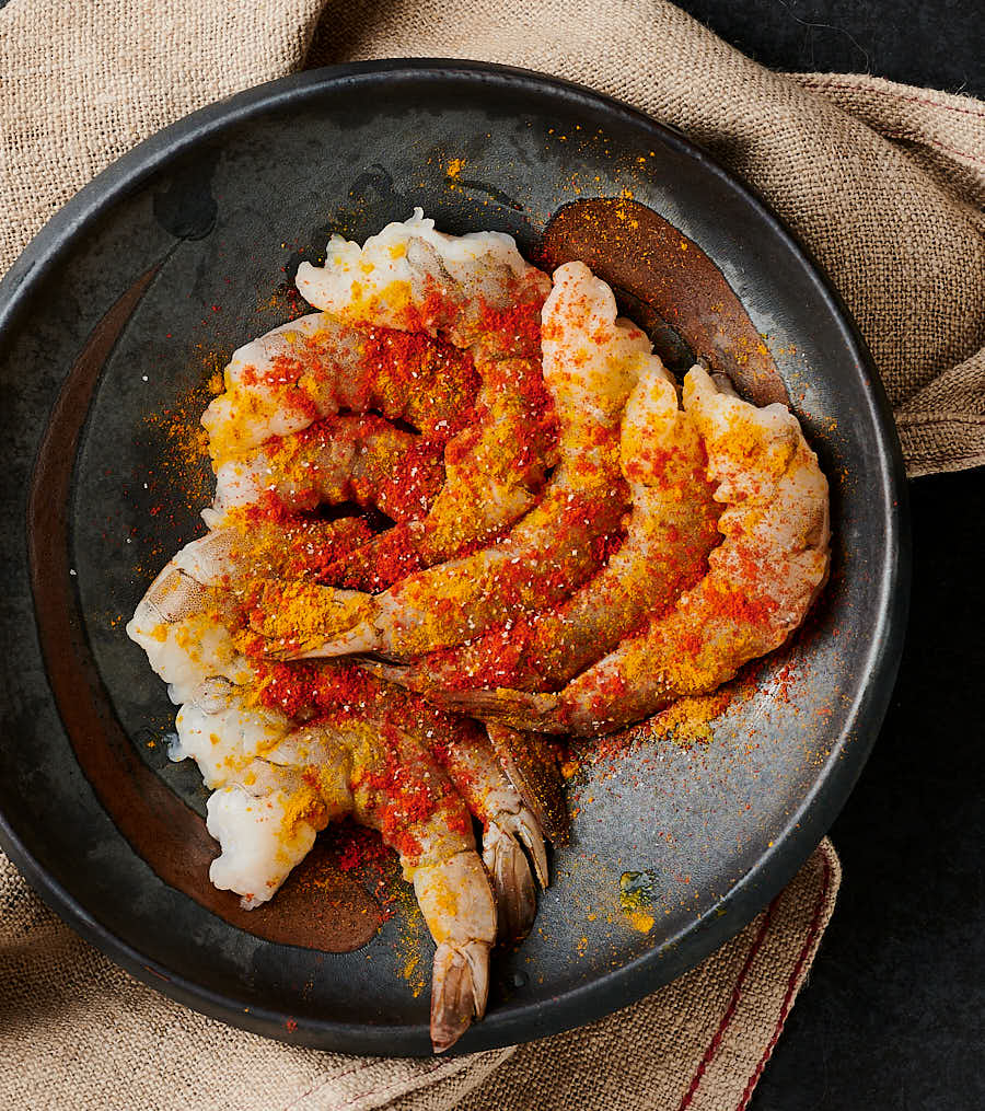 Seasoned raw shrimp in a bowl.