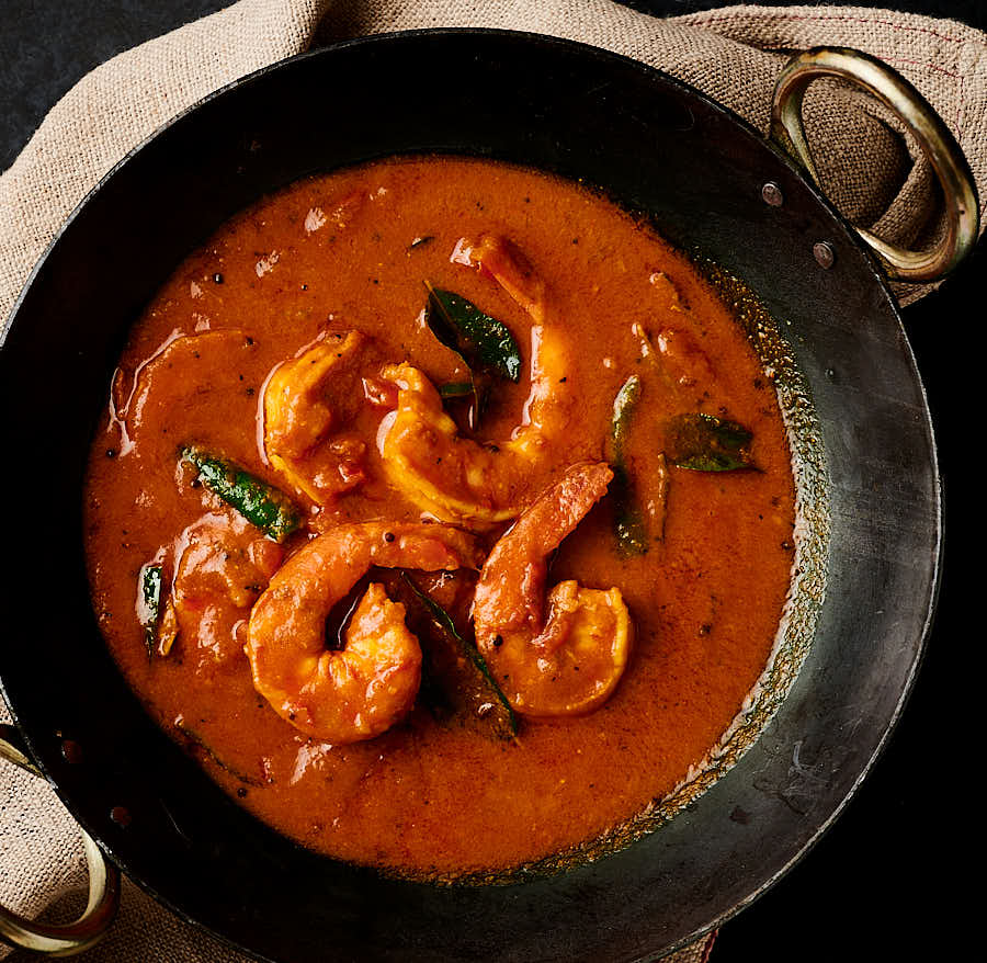 Prawn curry in a black kadai pan from above.